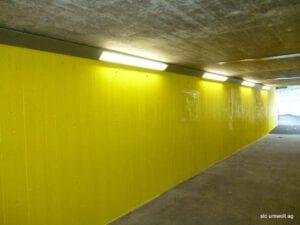 Betonwand beschichtet mit gelber Farbe und entferntem Graffiti