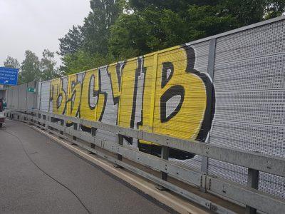 Lärmschutzwand an Autobahn mit gelbem Graffiti